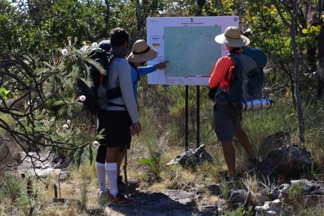 Grupo se orienta na placa com mapa durante a travessia. Foto: Duda Menegassi.