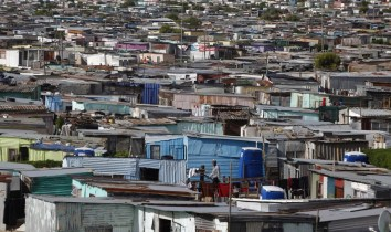 Residents walk through shacks in Cape Town's crime-ridden Khayelitsha township