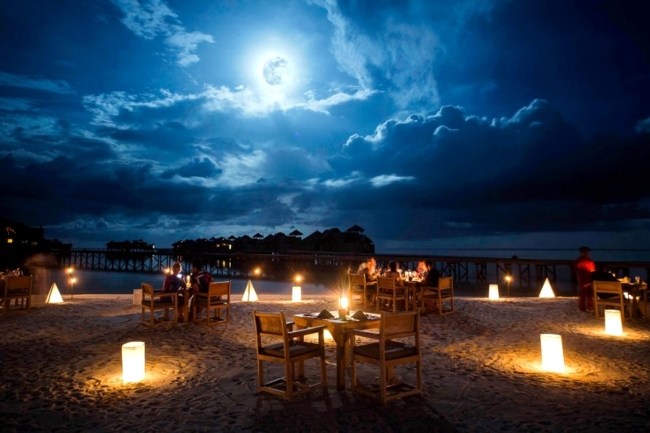 Perfect Picnic at the Beach with Clouds in the Sky and Table and Chairs with Luminarias
