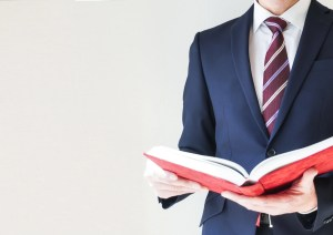 厚い本を手にするビジネスマン