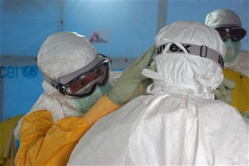 Centers for Disease Control and Prevention workers don protective gear before entering an Ebola treatment unit in Liberia on Aug. 17, 2014 (Photo: Athalia Christie).