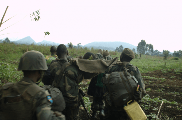 FARDC infantry carry an injured man a couple of hundred meters from the front line on a makeshift stretcher. Very rudimentary medicine—a tourniquet for his gunshot leg and an injection for pain relief. They had to carry him around three kilometers back to where the doctor tended to him (Photo: Joseph Kay).