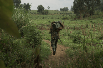 A FARDC soldier crosses open space under fire to carry ammunition to the front line northwest of Goma (Photo: Joseph Kay).