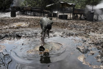 A man collects polluted water at an illegal oil refinery site near river Nun in Nigeria's oil state of Bayelsa November 27, 2012. Thousands of people in Nigeria engage in a practice known locally as 'oil bunkering' - hacking into pipelines to steal crude then refining it or selling it abroad. The practice, which leaves oil spewing from pipelines for miles around, managed to lift around a fifth of Nigeria's two million barrel a day production last year according to the finance ministry (Photo: Akintunde Akinleye / Reuters).