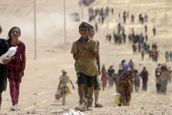 Refugee children from the minority Yazidi sect make their way towards the Syrian border, on the outskirts of Sinjar mountain, on August 10, 2014 (Photo: Rodi Said / Reuters).