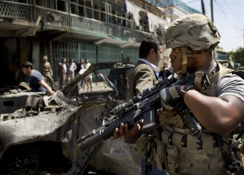 A U.S. soldier arrives to the scene where a suicide car bomber attacked a NATO convoy in Kabul, Afghanistan, Thursday, May 16, 2013. A Muslim militant group, Hizb-e-Islami, claimed responsibility for the early morning attack, killing many in the explosion and wounding tens, police and hospital officials said. The powerful explosion rattled buildings on the other side of Kabul and sent a pillar of white smoke into the sky in the city's east (Photo: AP/Anja Niedringhaus).