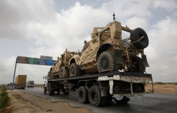 Trailer transports armored vehicles, used by NATO forces during the Afghan war, along a road after their arrival at Port Mohammad Bin Qasim, some 40 km from Karachi, in May 2013. After more than ten years, NATO and the U.S. have started withdrawal of their equipments from Afghanistan (Photo: Athar Hussain / Reuters).