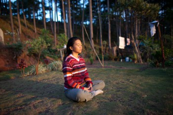 "Florence ""Dom-an"" Macagne Manegdeg and her morning ritual at the the Kasiyana Peace and Healing Center in Sagada. The mountains of Sagada have been a refuge for Manegdeg, whose husband was one of the hundreds of activists killed while Gloria Macapagal Arroyo was president. In 2010, Manegdeg turned her home in this farming village into a center for peace and healing, a respite for individuals who have experienced trauma and a center for those who are advocating and volunteering for peace and healing programs. (Photo by Mario Ignacio)"