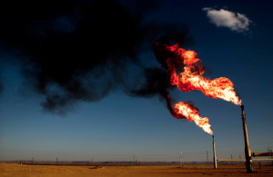 "A natural gas ""flare off,"" too expensive to utilize, colors the Sahara Desert's twilight sky."