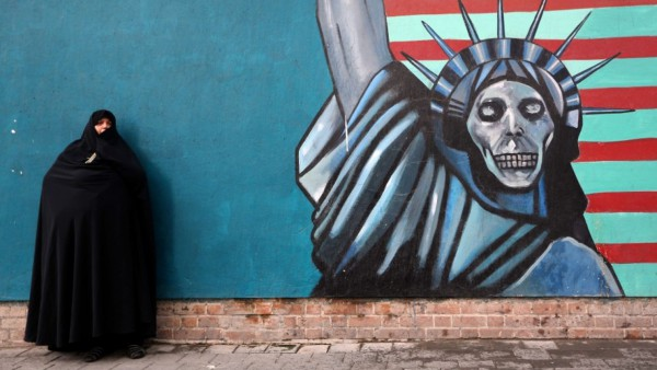 An Iranian woman stands in front of the painted wall of the former U.S. Embassy on Nov. 4 in Tehran, the scene of a demonstration to mark the anniversary of its storming by student protesters that triggered a hostage crisis.