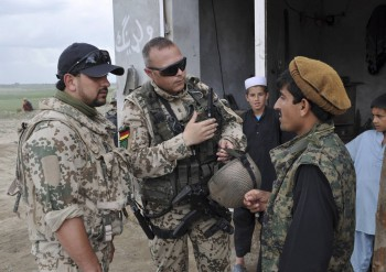 A German soldier, accompanied by an Afghan translator in a German uniform, talks to an inhabitant of the village Arab Sher Ali in northern Chahar Darrah in April 24, 2012. The soldiers wanted to find out about the mood among the Afghans, and were also looking for information after two Belgian soldiers were wounded by an IED the day before in neighbouring Qara Yatim village. The German military lost more soldiers in this region due to fights and attacks than at any other place since the end of  World War II. After years of fighting, the district is relatively stable now. But as international combat troops prepare to leave Afghanistan by the end of 2014, many Afghans in Chahar Darrah fear the return of the Taliban (Photo: Sabine Siebold, Reuters).