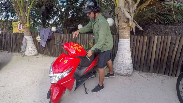 Michael getting on their rental scooter to explore the island of Cozumel, one of the best things to do in Cozumel