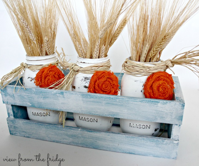 This Easy Fall DIY Centerpiece is a perfect Fall decor accent for the home. Use it to decorate the table, fireplace mantel or as fall front porch decor! The distressed mason jars are accented with easy to make burlap rosettes! OHMY-CREATIVE.COM