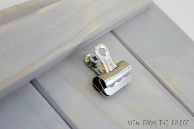 How to attach a bulldog clip to the front of the plaque with a short screw
