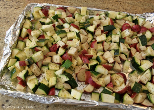 A foil lined cookie sheet with chopped Potatoes And Zucchini ready to go in the oven