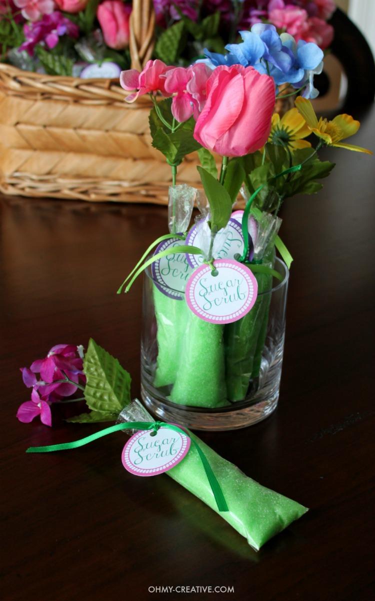 Homemade Sugar Scrub Shower Favors in a glass vase as a centerpiece