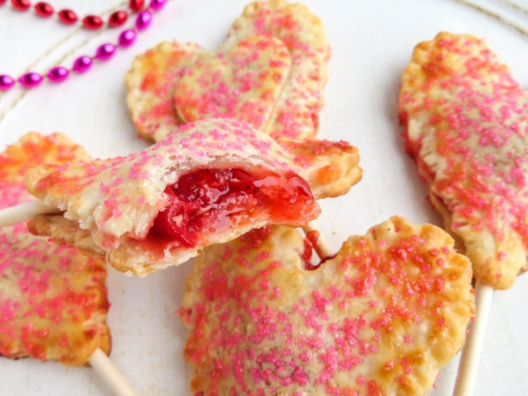 Mini Cherry Pies - Heart Pie Pops - A sweet Valentine's Day Treat! OHMY-CREATIVE.COM | Heart Shaped | Valentine's Day Dessert | Pie Pops | Pie Crust | Cherry Pie | Pillsbury Pie Crust | Premade Pie Crust | Sprinkles | Handheld pies | Mini Pies | Heart