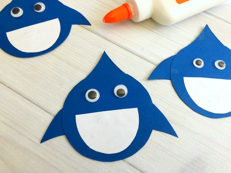 Glue white pieces of paper to the blue sharks and add googly eyes.