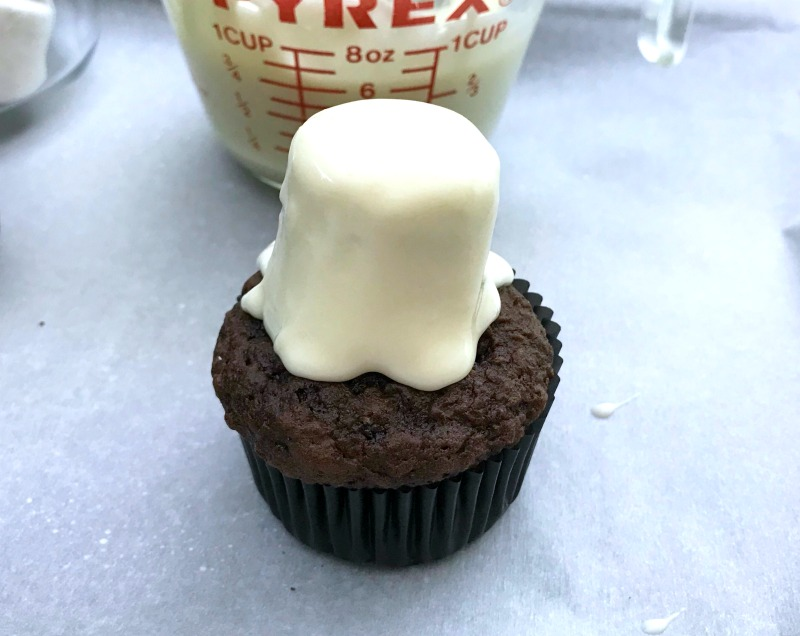 Assembling top of ghost cupcakes for halloween party. These Marshmallow Ghost cupcakes for Halloween are an EASY semi-homemade treat! OHMY-CREATIVE.COM   #marshmallowghostcupcakes #ghostcupcakes #ghost #halloweentreat #halloweendessert #halloween