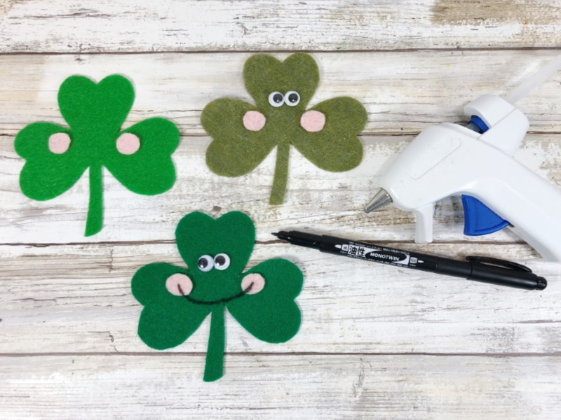 Attach wiggle eyes with glue or glue sticks to the top center of the Shamrock, placing them right beside each other.