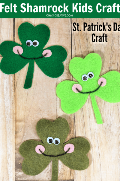 Finished felt shamrock craft with smiling faces and googly eyes.