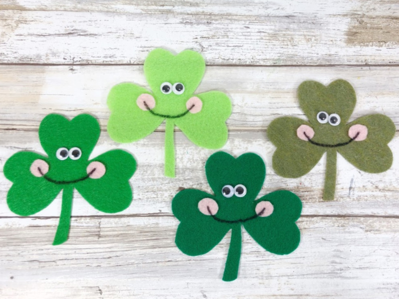 Finished felt Kawaii shamrock craft with smiling faces and googly eyes.