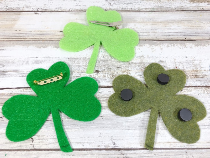 Finished felt shamrock craft with smiling faces and googly eyes. Options to add pin or magnet backing to shamrocks.