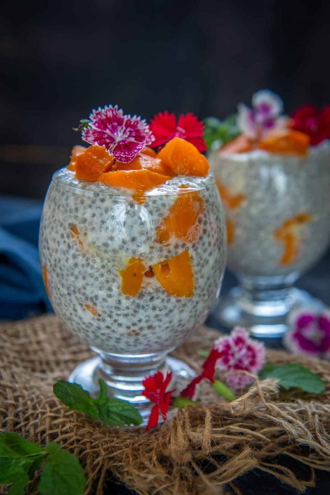 Mango chia pudding decorated with pink tropical flowers.