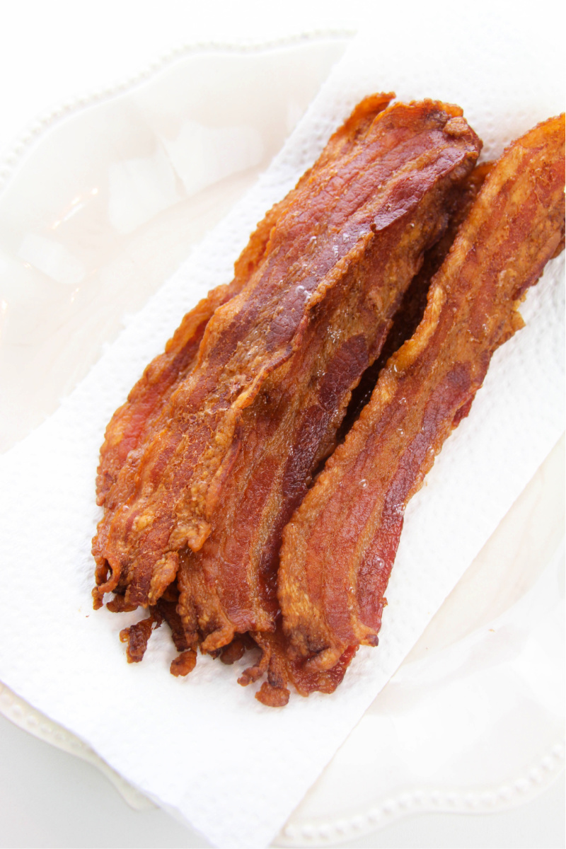 Crispy bacon placed on a paper towel to absorb extra bacon grease.
