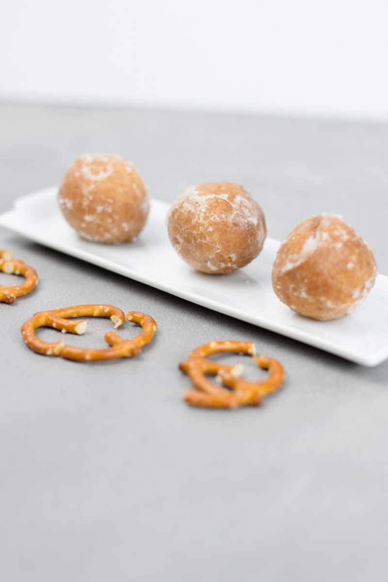 The donut holes are placed on the white platter with the pretzel haves ready to be use as the reindeer antlers.