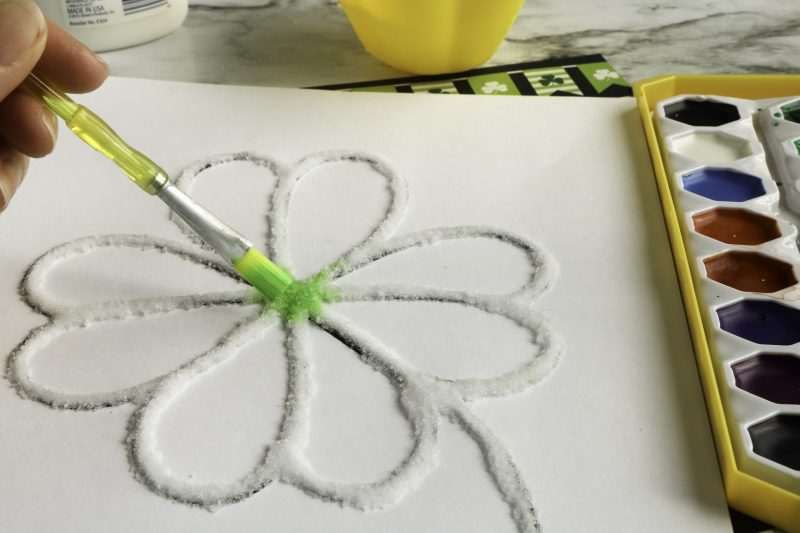 Once the salt is sprinkled on the glue touch the paintbrush with paint onto the raised salt.