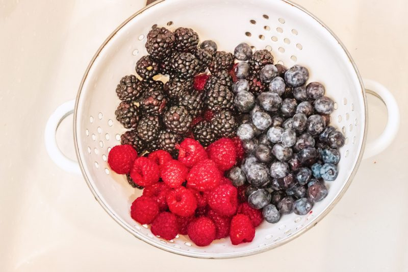 Washed raspberries, blackberries and blueberries in a white strainer.
