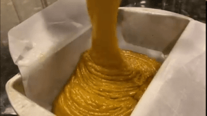 pumpkin bread batter being poured in a parchment lined loaf pan