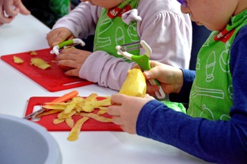two children peeling potatoes on red cutting mats