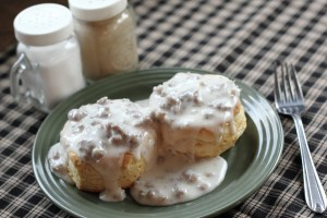 biscuits and sausage gravy on a green plate on a checkered tablecloth
