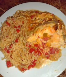 Queso Chicken with Spanish Rice on a white plate sitting on a marble table
