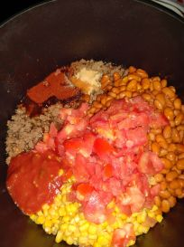 chili ingredients including cooked hamburger, diced tomatos, beans and salsa