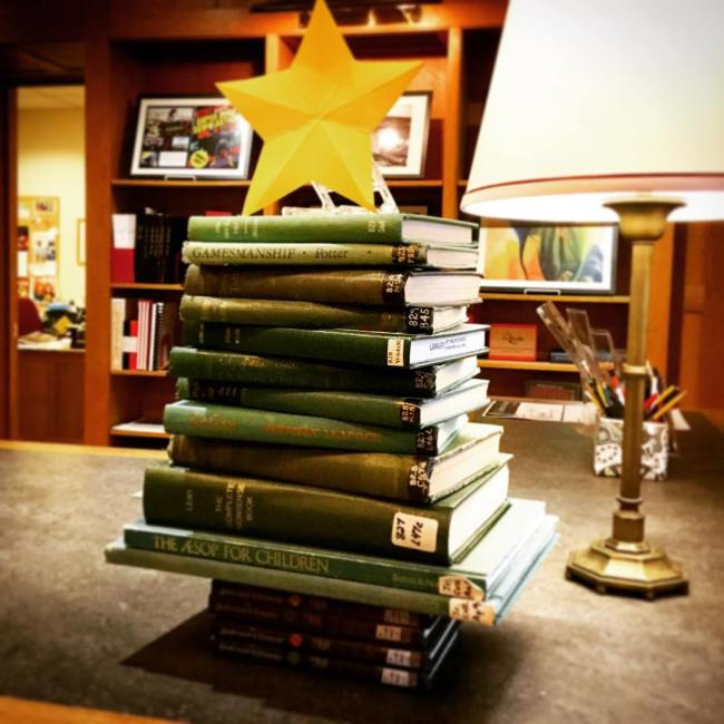 The book tree is back - adorning the front desk to welcome students back for the beginning of Winter Term. #ohrstromlibrary #booktree #greenbooks #star #bookdisplay #library #librariesofinstagram #librarydisplay