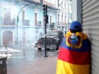 A man stands wrapped in the national flag as an armoured personnel carrier is seen during protests after Ecuadorian President Lenin Moreno's government ended four-decade-old fuel subsidies, in Quito, Ecuador October 3, 2019. REUTERS/Daniel Tapia