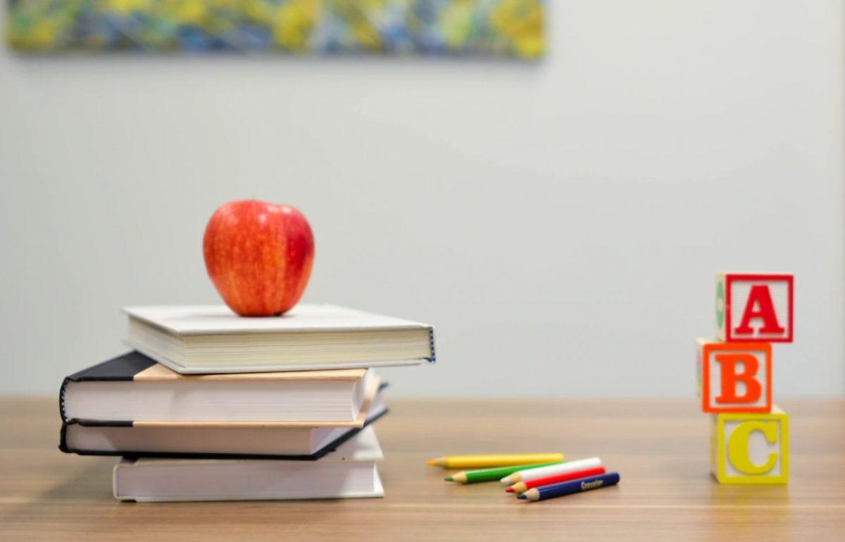 una manzana y lápices en una escuela (Imagen: Unsplash)