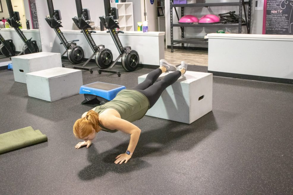 Heather doing a push up with her feet on a box at Kaia Fit