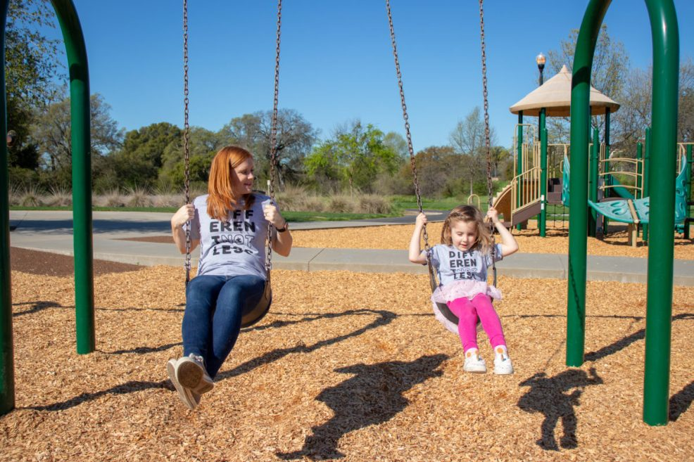 mother and daughter on swing at the park