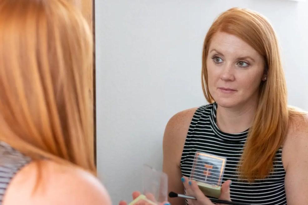 Heather looking in mirror applying makeup