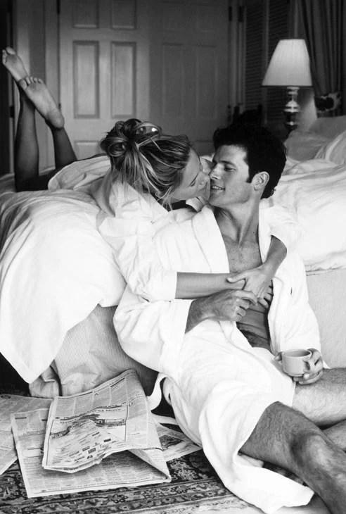 hombre y mujer, ella recostada en la cama y el sentado en el suelo mientras se abrazan y toman café