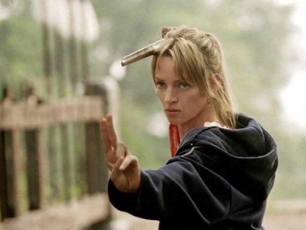 Escena de la pelícla kill bill uma turman sosteniendo una espada en su mano