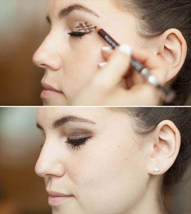 Chica dibujandose un hashtag en los ojos para lograr el efecto smokey-eyes