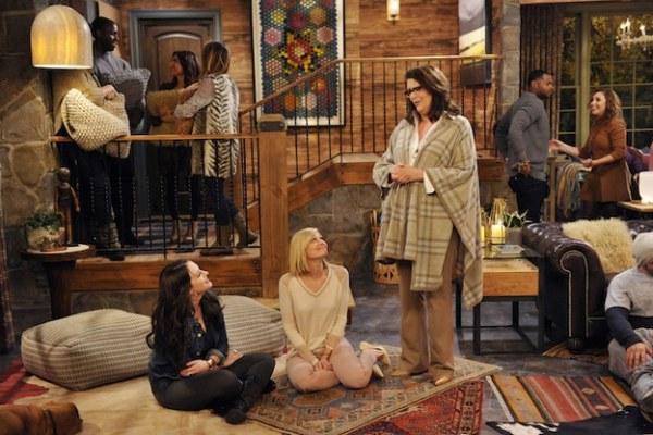 Escena de la serie two broke girls chicas sentadas sobre la alfombra mientras conversan con una mujer