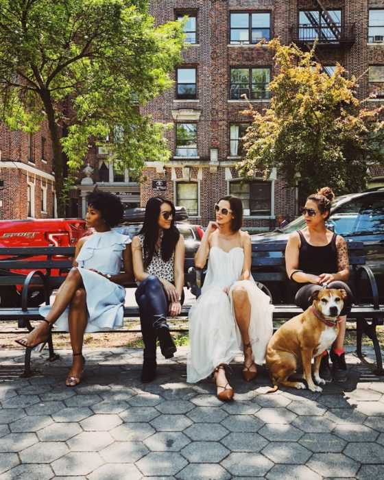 Grupo de cuatro mujeres sentadas en la banca de un parque charlando
