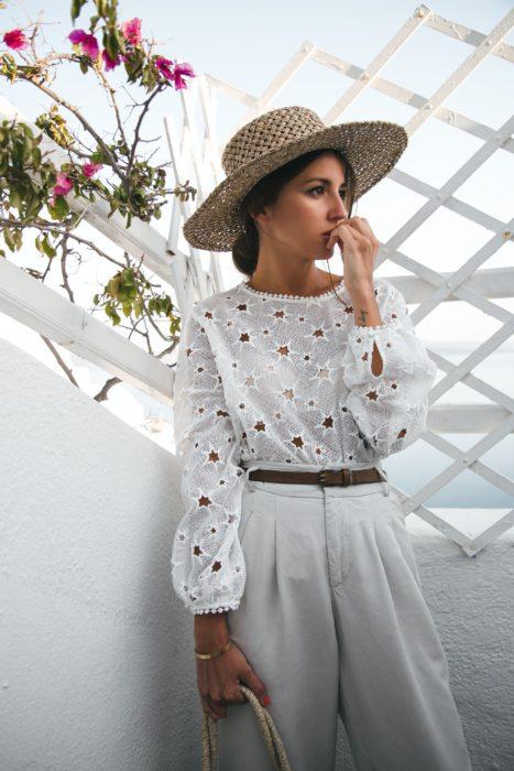 Looks de primavera; chica con rostro preocupado usando sombrero grande de mimbre, con blusa de encaje blanco con formas de estrellas y pantalón a la cintura blanco con cinto café