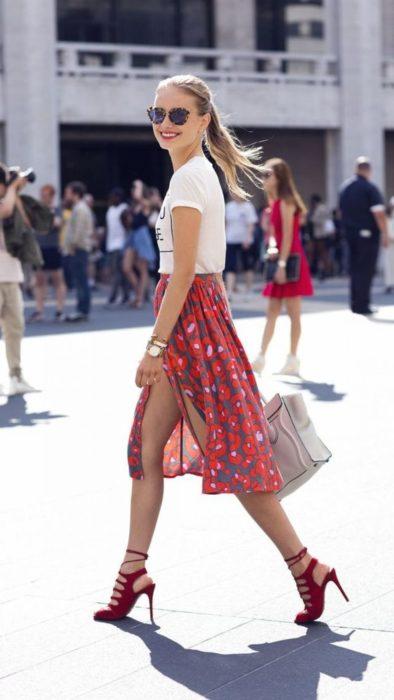 Looks de primavera; chica feliz caminando en la calle, con cabello rubio recogido en una coleta, lentes de animal print, blusa básica blanca, falda floreada con abertura y zapatos de tacón rojos